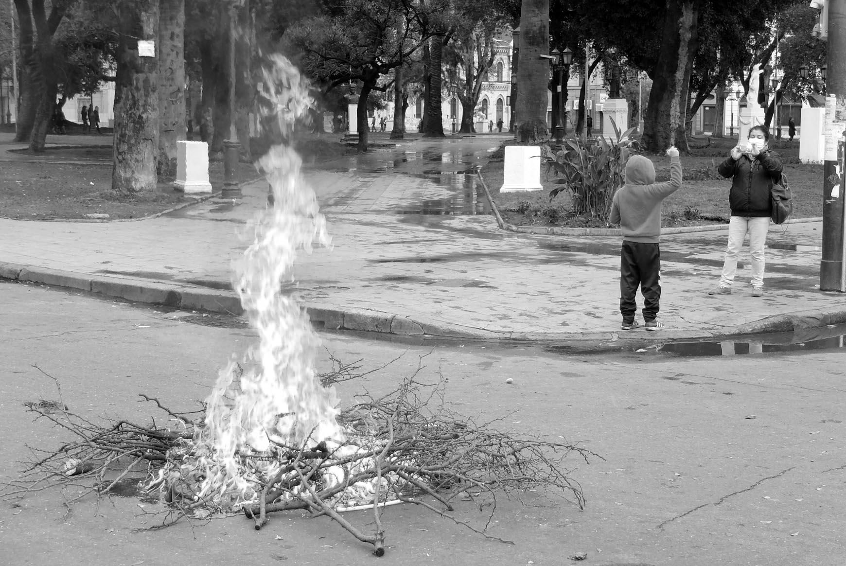 Una mujer fotografía a su hijo puño en alto frente a una de las pocas fogatas que se encendieron en la protesta.