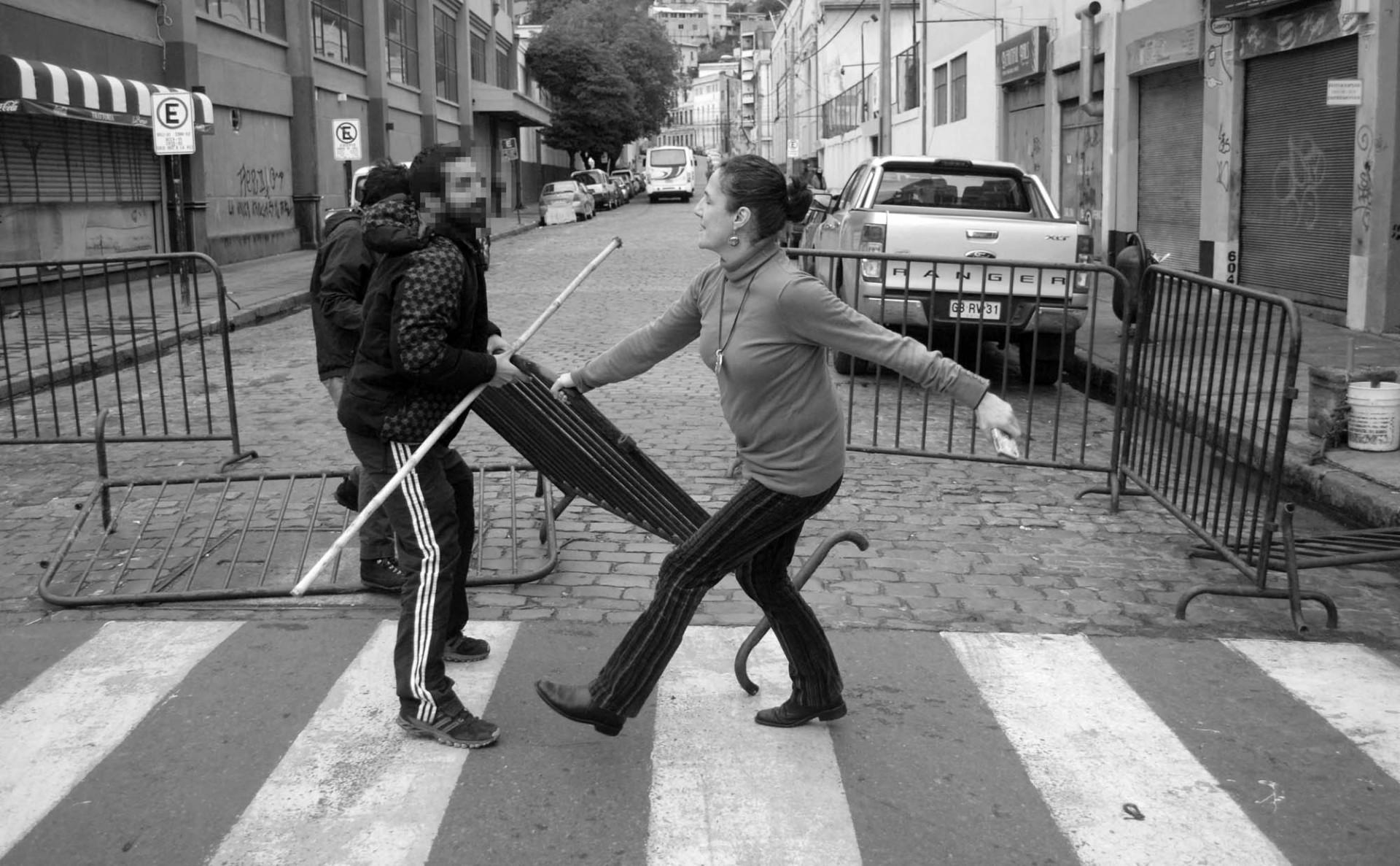 Una mujer intenta impedir que un joven saque de su lugar una barrera policial al final de la protesta. Foto: Dedvi Missene.