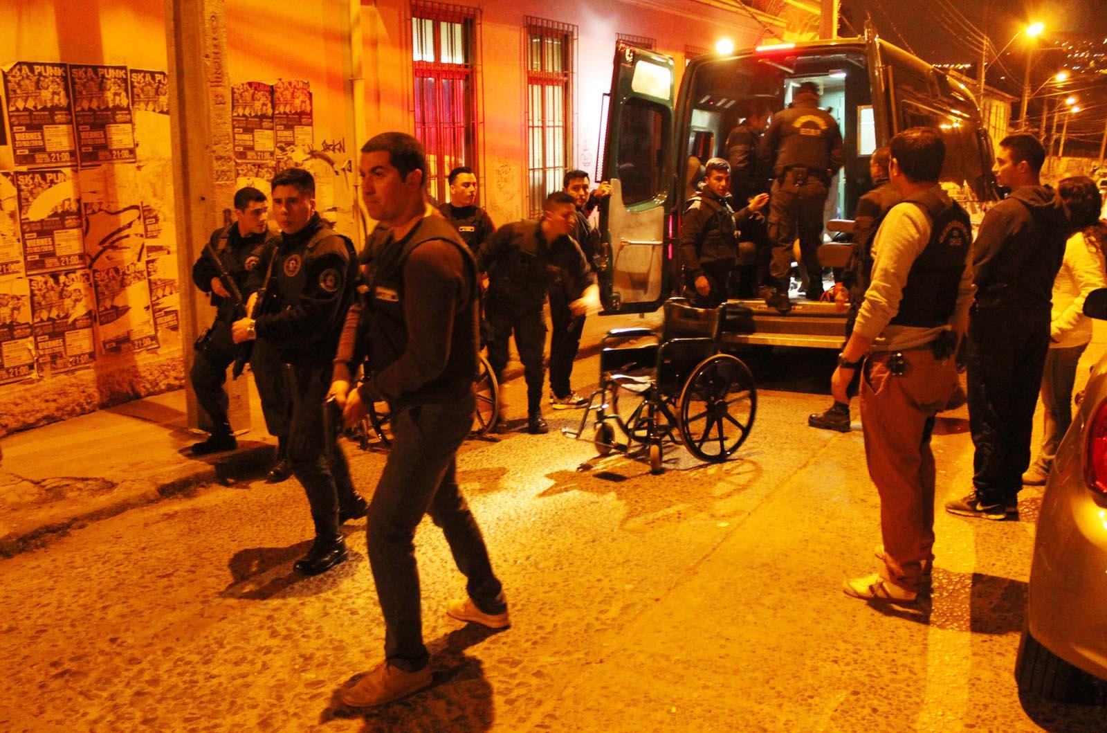 Un grupo de reos es evacuado bajo la atenta mirada de gendarmes armados.